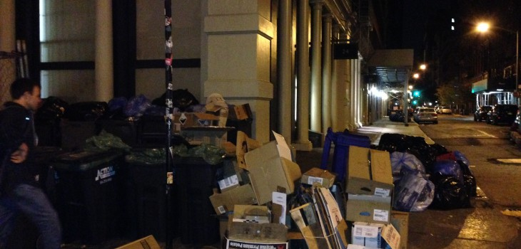 A pile of garbage on the curb of a street at night in New York City.