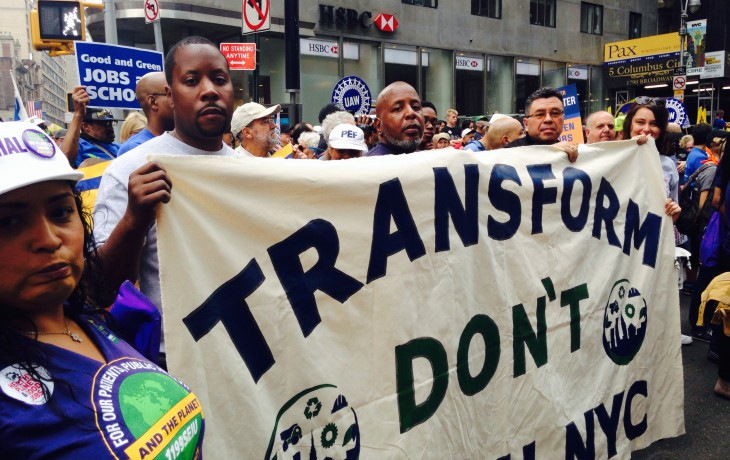 "A group of TDTNYC members holding a ""Transform Don't Trash NYC"" sign at a rally."