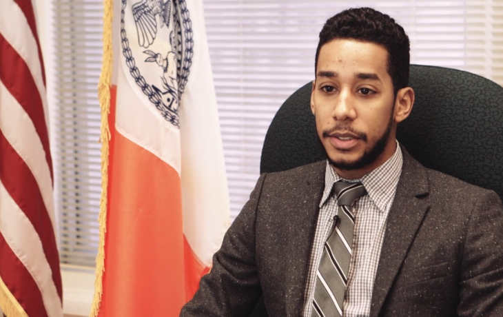 Council member Antonio Reynoso sitting in a suit in his office, speaking.