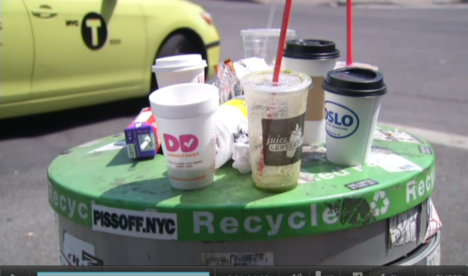 Empty plastic and styrofoam cups and bottles sitting on top of a green-toped recycling canister as a yellow-green taxi goes by.